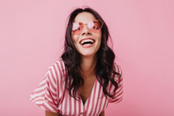 Emotional latin girl in sparkle sunglasses laughing to camera. Adorable female model enjoying photoshoot in pink clothes