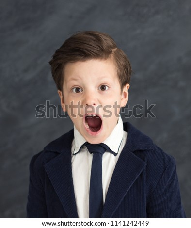 Emotional little businessman shouting. Small boy in suit feeling disappointment and shock, studio portrait #1141242449