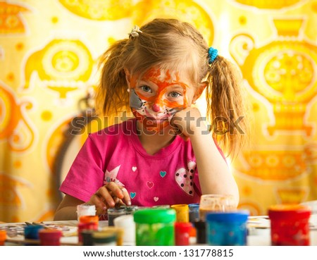 Emotional little child, drawing paint with paint of face