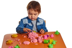 Emotional little child girl playing with kinetic sand on the orange table. Isolated white background