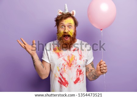 Emotional male has image of unicorn, gestures actively, has surprised expression, dirty face and t shirt, exclaims emotionally, holds balloon, entertains guests on party, suggests creative contest