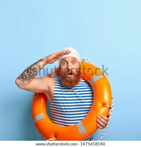 Emotional male lifeguard stares into distance, notices sinking person at sea, helps people to survive, carries inflated lifebuoy, stares with bugged eyes, wears rubber swimming cap, isolated on blue #1475658140