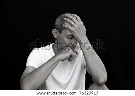 emotional man cowering in grief against black background