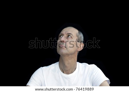 emotional man cowering in grief against black background