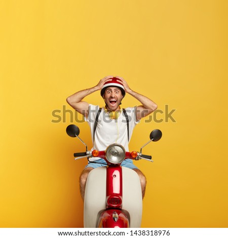 Emotional man driver gets in accident on road during motorbike ride, yells from negative emotions, keeps hands on head protected with helmet, wears casual white t shirt, rucksack, isolated on yellow