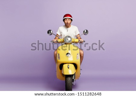 Emotional man driver poses on yellow motorbike, wears protective headgear and white t shirt, shocked with very high speed on his route, isolated over violet background. Reaching destination.