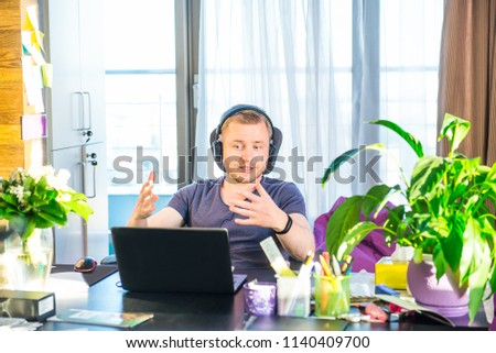 Emotional man in headphones looking at computer screen, gestures and participating in online meeting, conference with business partners, remote job interview, learning languages, consulting clients