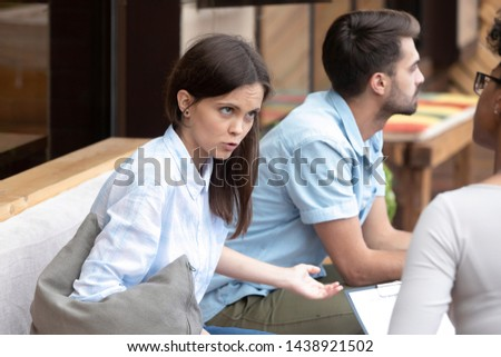 Emotional millennial girl talk about relationships problems share thoughts with female psychologist, couple visit marriage counsellor or family relations expert consulting before breakup or divorce #1438921502