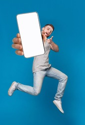 Emotional millennial redhaired guy pointing finger at camera, jumping with mobile phone on blue studio background, mockup for mobile app on white screen. Creative collage with website template