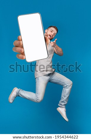 Emotional millennial redhaired guy pointing finger at camera, jumping with mobile phone on blue studio background, mockup for mobile app on white screen. Creative collage with website template Stock photo ©