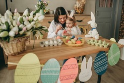 Emotional mother and daughter on hands at table coloring colored Easter eggs in bunny ears and flowers on table in kitchen