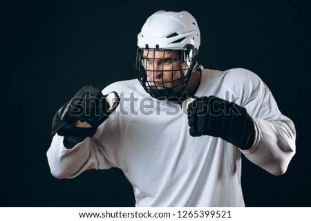 Emotional outraged ice-hockey player man gestures angrily, being provoked with the enemy, standing in fight pose. Sport, Negative emotions and rivalry concept #1265399521