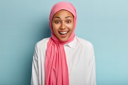 Emotional overjoyed Muslim woman laughs happily, has pleased expression, expresses sincere feelings, wears pink headwear, shows white teeth, isolated over blue background. Human emotions concept