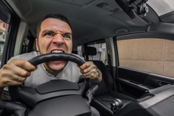 Emotional person. The driver of the car screams at someone in the traffic jam. Concept hysterics and broken car