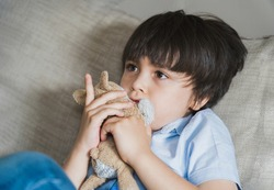 Emotional portrait  kid hugging dog toy sitting on sofa wathcing TV, Young boy siting on couch looking out with thinking face or nervous, Children Health care