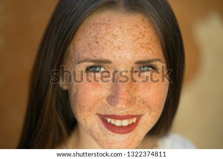 Emotional portrait of a cheerful and cheerful beautiful girl with freckles on her face and blue eyes looking with a smile at the sun against the background of limestone yellow rock. Summer vacation #1322374811