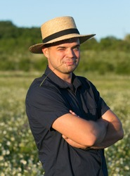 Emotional portrait of a cheerful and funny country young man in a straw hat looking up, screwing up his eyes on the camera while standing in a field at sunset. Peasant. Summertime. Summer. Lifestyle