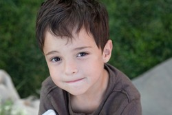 Emotional portrait of a small child. Eye contact. Caucasian. Smiling face. An attentive look. Beautiful brown eyes, long eyelashes. Handsome boy 6 years old. Outside. Close up.