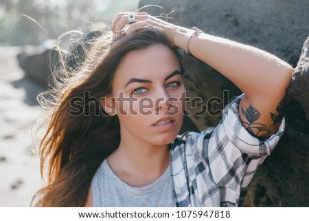 Stock Photo Emotional portrait of Fashion stylish portrait of pretty young hipster blonde woman,going crazy,elegant black hat,soft colors,cool crazy  girl.Red urban wall background.surprised girl close up, tattoo
