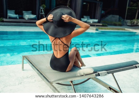 Emotional portrait of Fashion stylish portrait of pretty young hipster blonde woman posing in the swimming pool. hat, swimsuit, outdoor fashion portrait ,going crazy,elegant black hat cool -  stock photo