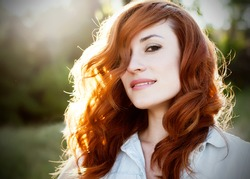 Emotional portrait of happy beautiful woman with red curly hair and natural makeup enjoying her life in nature. Soft sunny colors. Outdoor shot. Copyspace.