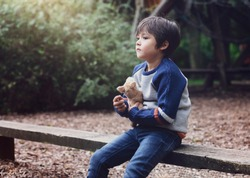 Emotional portrait of Lonely kid hugging dog toy sitting alone in the playground, Sad child sitting with his toy with looking deep in through, little boy playing alone with  thinking face.