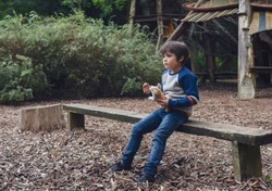 Emotional portrait of Lonely kid hugging dog toy sitting alone in the playground, Sad child sitting with his toy with looking deep in through, A boy playing alone with  thinking face,Mental healt
