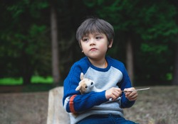 Emotional portrait of Lonely kid hugging dog toy sitting alone in the playground, Sad child sitting with his toy with looking deep in through, A boy playing alone with  thinking face,Mental health