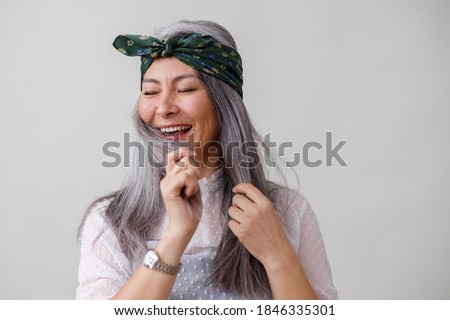 Emotional portraits of a paled long hair asian matured woman on grey background Photo stock ©