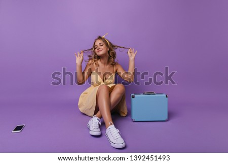Emotional pretty girl sitting on the floor with inspired smile. Indoor photo of fascinating female model posing beside blue valise.