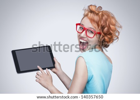 Emotional red-haired girl with red glasses holding and  touching tablet computer. Broad beautiful attractive smile with teeth.  Empty space on the tablet pc, you can place your text. Gray background