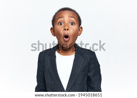 Emotional scared black little boy gasping and raising eyebrows seeing something scary. Emotional African child expressing shock, astonishment or fear, being speechless because of stupefaction Photo stock ©