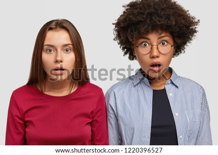 Emotional shocked young European women have bated breath, stare with bugged eyes, stare thrilled and astonished, stand closely, isolated over white background, afraid of something. Emotions concept #1220396527