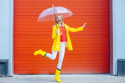 Emotional woman dancing laughing under umbrella in yellow raincoat, rubber boots, red t-shirt over red garage door background. Cool expression on face. Outdoor. Full height. Weather forecast concept