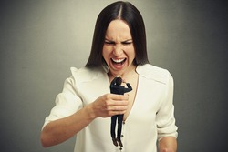 emotional woman holding in fist small scared man and yelling at him. photo on dark background
