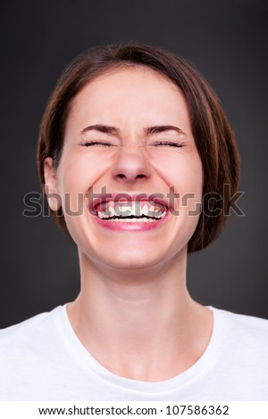 emotional woman is laughing loudly over dark background