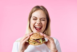 Emotional woman on a pink background eating fast food hamburger