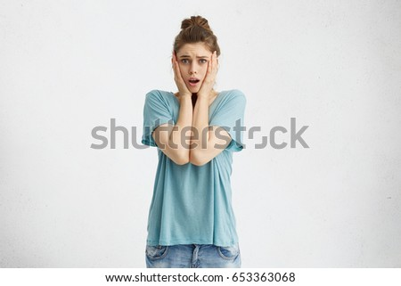 Emotional worried young female in casual clothes holding hands on her cheeks, opening mouth, feeling perplexed and frustrated after she left home without having unplugged iron. Human emotions