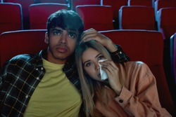 Emotional young couple, attractive man and woman sitting at the cinema, watching sad movie together. Girlfriend wiping tears while her boyfriend stroking her hair. Relationship, entertainment concept