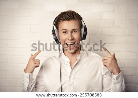 Emotional young man in white shirt listening to music in headphones with excitement.