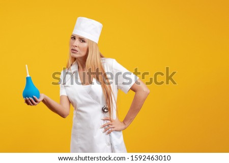 Emotional young woman doctor nurse in a white coat and hat with a douche enema in hands posing on a yellow background