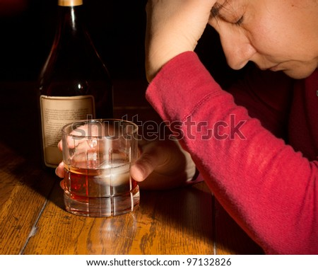 Emotionally distraught woman with a glass of whiskey and bottle