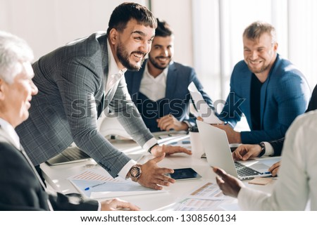 Emotionally excited multiracial businessmen discussing business documents, vivid real emotions and people in common everyday business routine situations