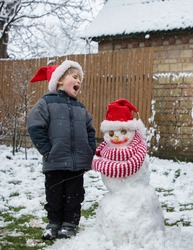 emotionally screaming toddler boy and snowman wearing Santa hat and bright red striped scarf. winter holiday mood, seasonal outdoor activities, carefree childhood