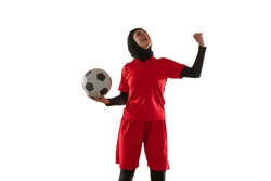 Emotions. Arabian female soccer or football player on white studio background. Young woman celebrating goal or match winning, catched in motion, action. Concept of sport, hobby, healthy lifestyle.