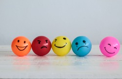 Emotions balls background, Happy Smiley faces ball in yellow , orange and pink. Sadness ball in blue and madness ball in red. Self made hand draw balls.