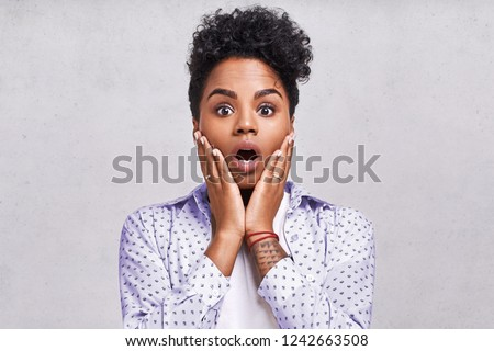 Emotions concept. Nervous emotional scared young lovely African American female stares at camera and opens mouth wide, notices phobia, expresses her fear against something, poses alone indoor. #1242663508