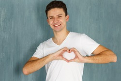 Emotions man. Man showing hand sign heart on his chest. Joy, happiness, love - sincere emotions young man. Concept - for the charity, fund support world. Man making a heart shape with his hands.