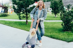 Emotions of a mom fooling around with a little daughter. Mom twirling her daughter outside. Mommy's carefree happy walk with her baby.