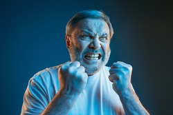 Emotions of a television fan. Screaming, hate, rage. Crying emotional angry man screaming in colorful bright lights at studio. Emotional, mature face. Human, facial expression concept.